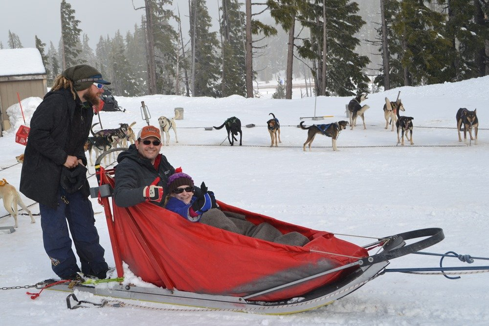 "Snuggled in the ""basket"" of a sled, Mike and Bethy VanCleave get ready to mush at Mount Bachelor in Central Oregon."